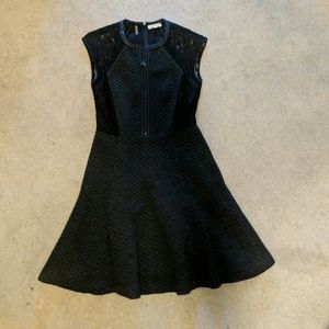 Black dress with leather trim. Fit and flare.